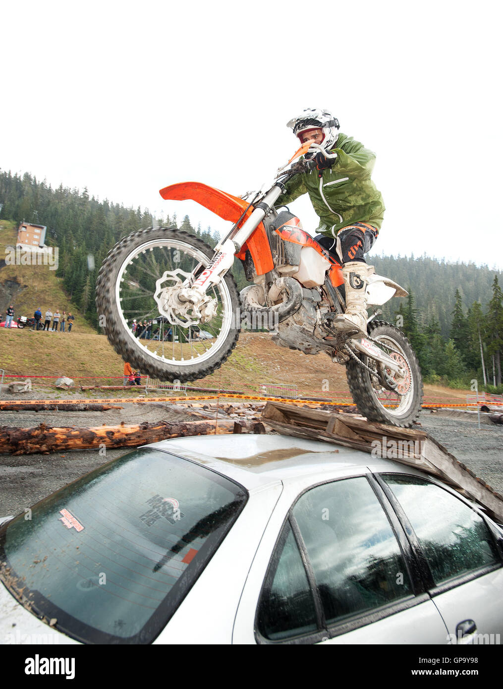 A dirt biker jumps his bike over a wrecked car at the Whistler Olympic Park.  Whistler BC, Canada - Stock Image