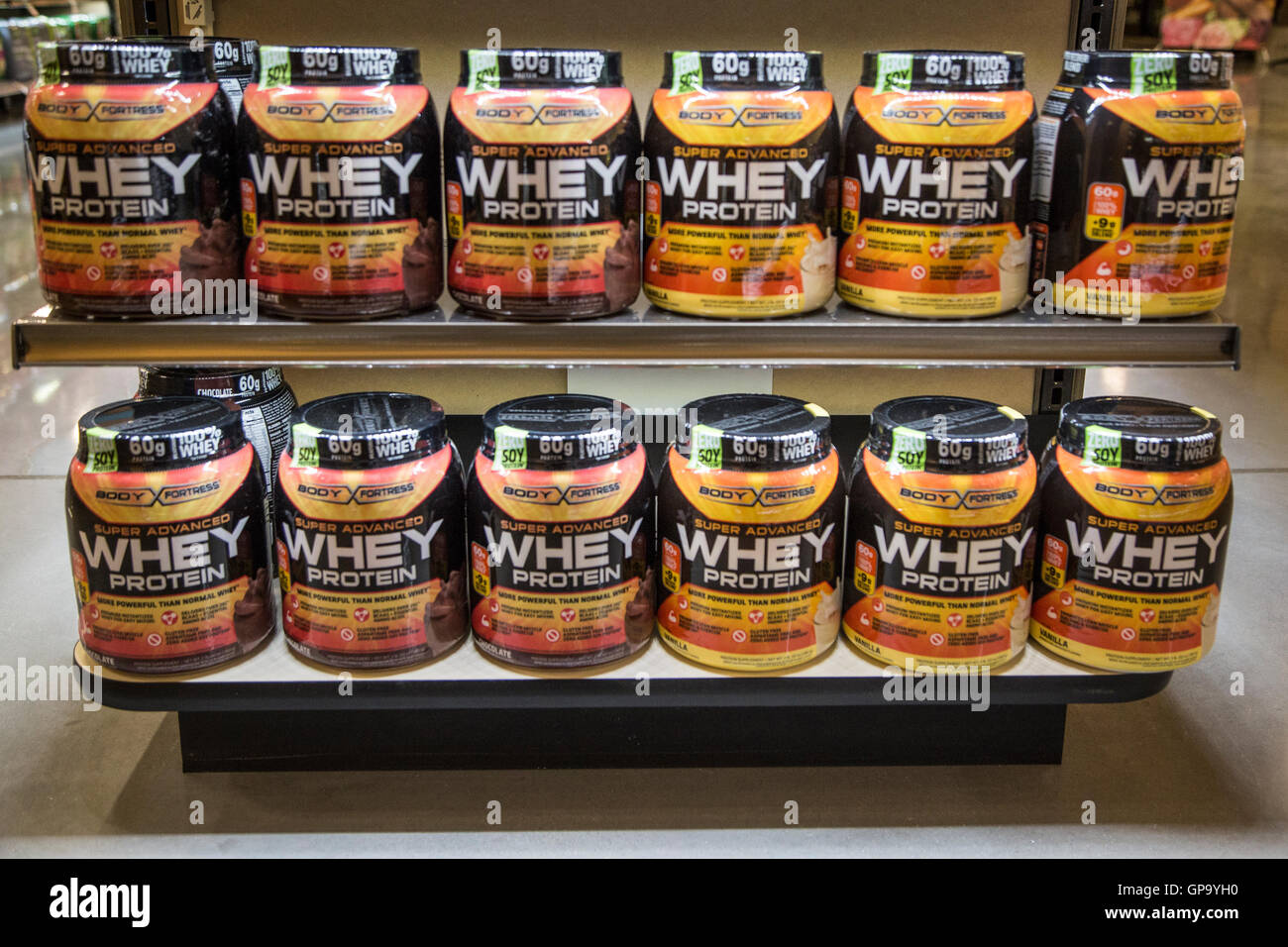 Large plastic containers of whey protein for sale on the shelves of a health food store. - Stock Image