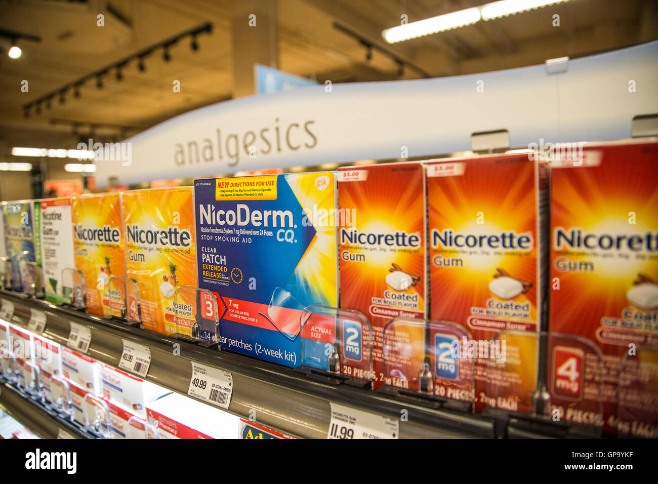 boxes of NicoDerm and Nicorette products on the shelf of a pharmacy - Stock Image