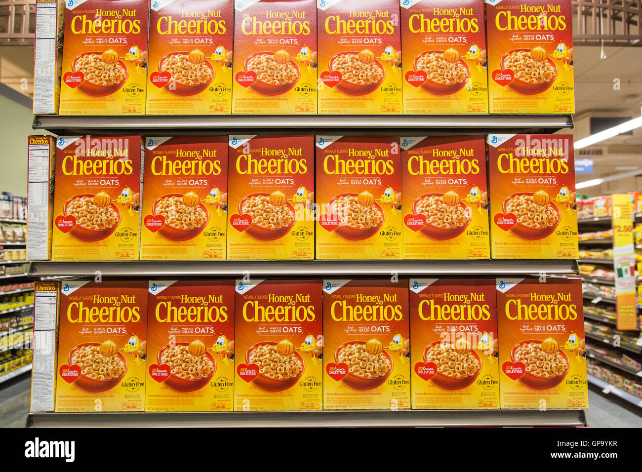 Boxes of General Mills Honey Nut Cheerios cereal on display at on grocery store shelves - Stock Image