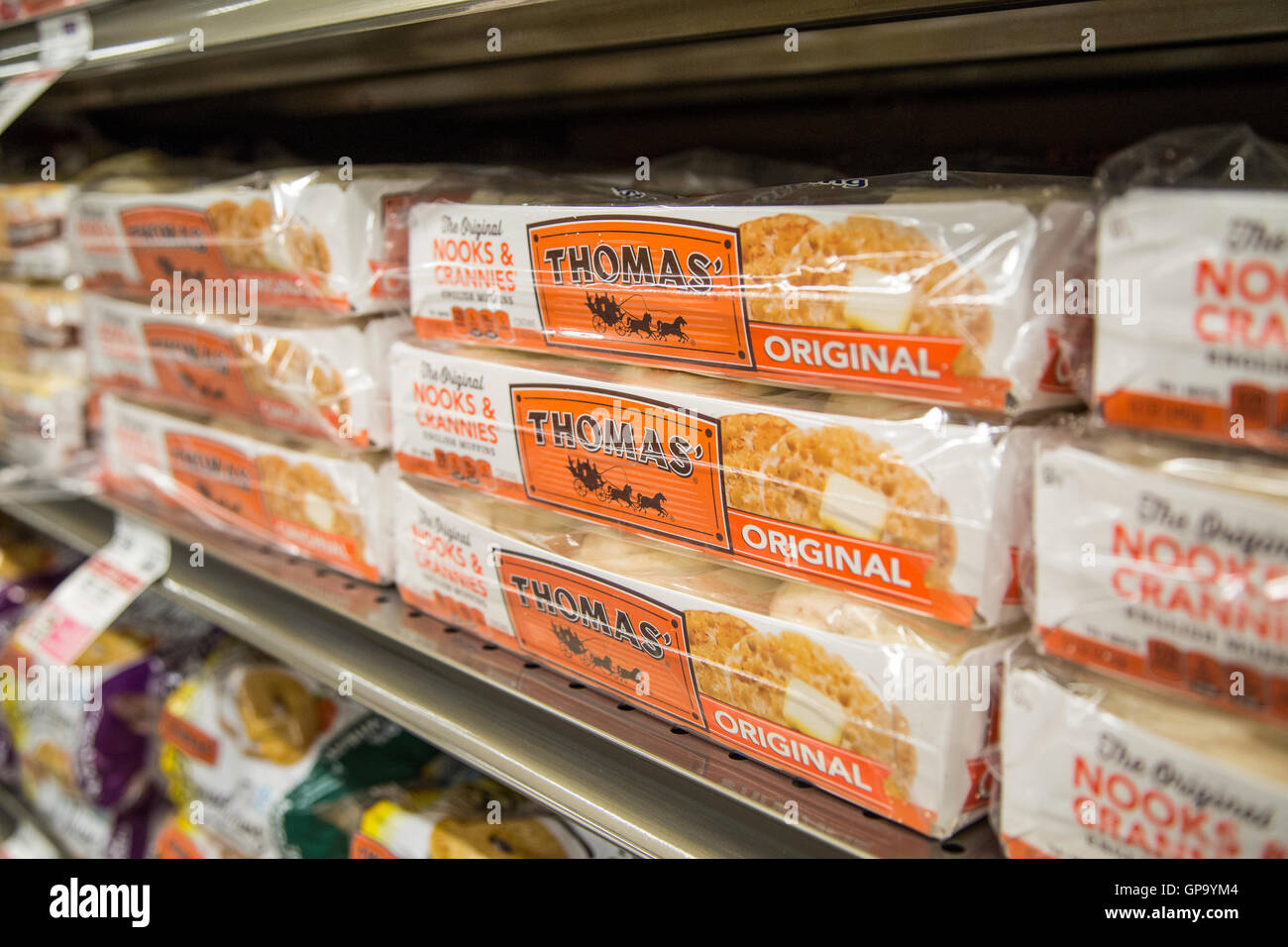 Packages of english muffins on a grocery store shelf - Stock Image