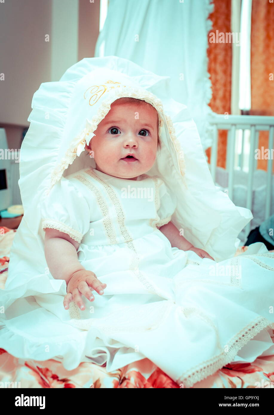 Little Baby Girl Wearing A Beautiful White Dress Waiting For Baptism