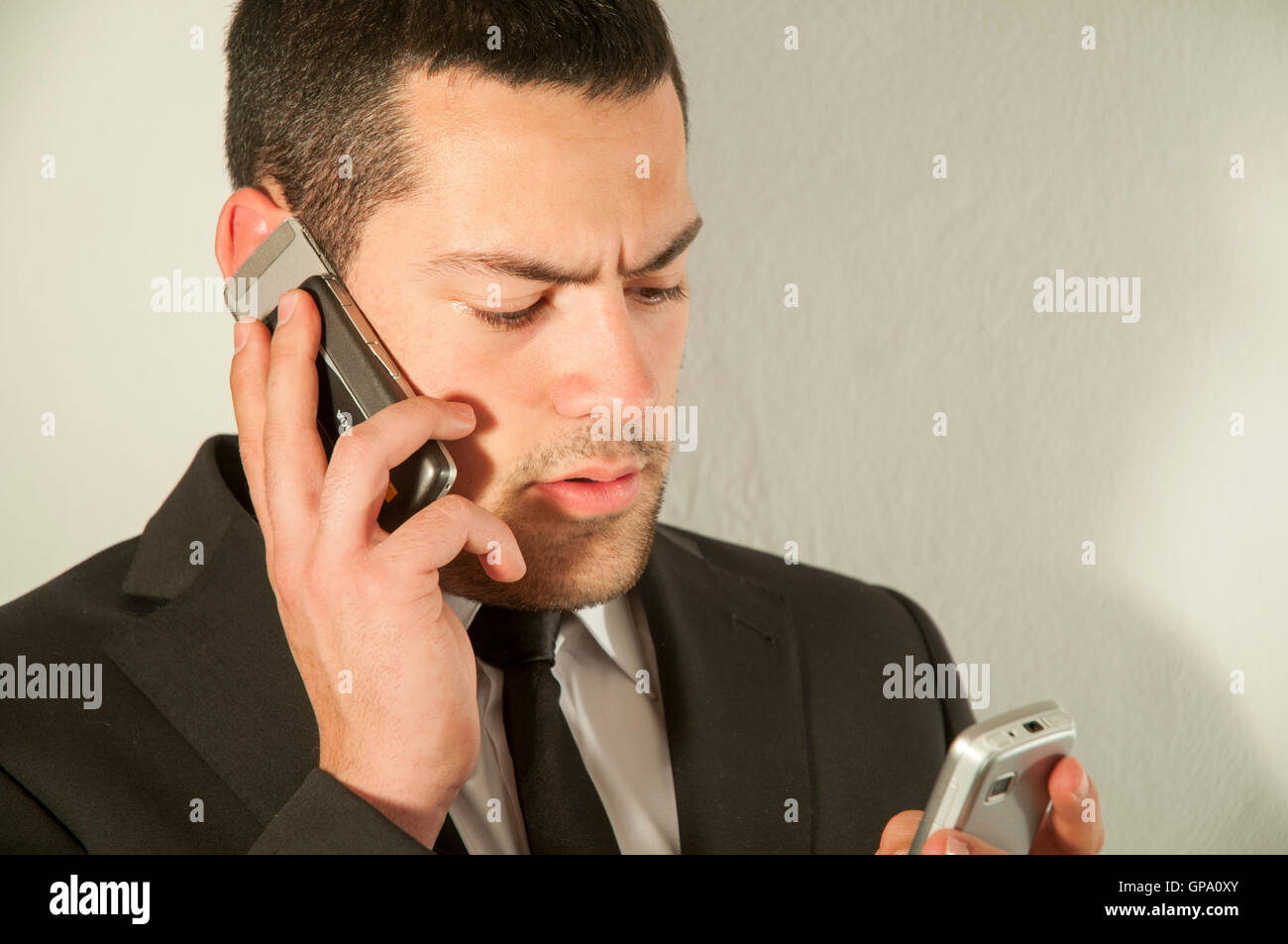 Young man using two mobiles phones. - Stock Image