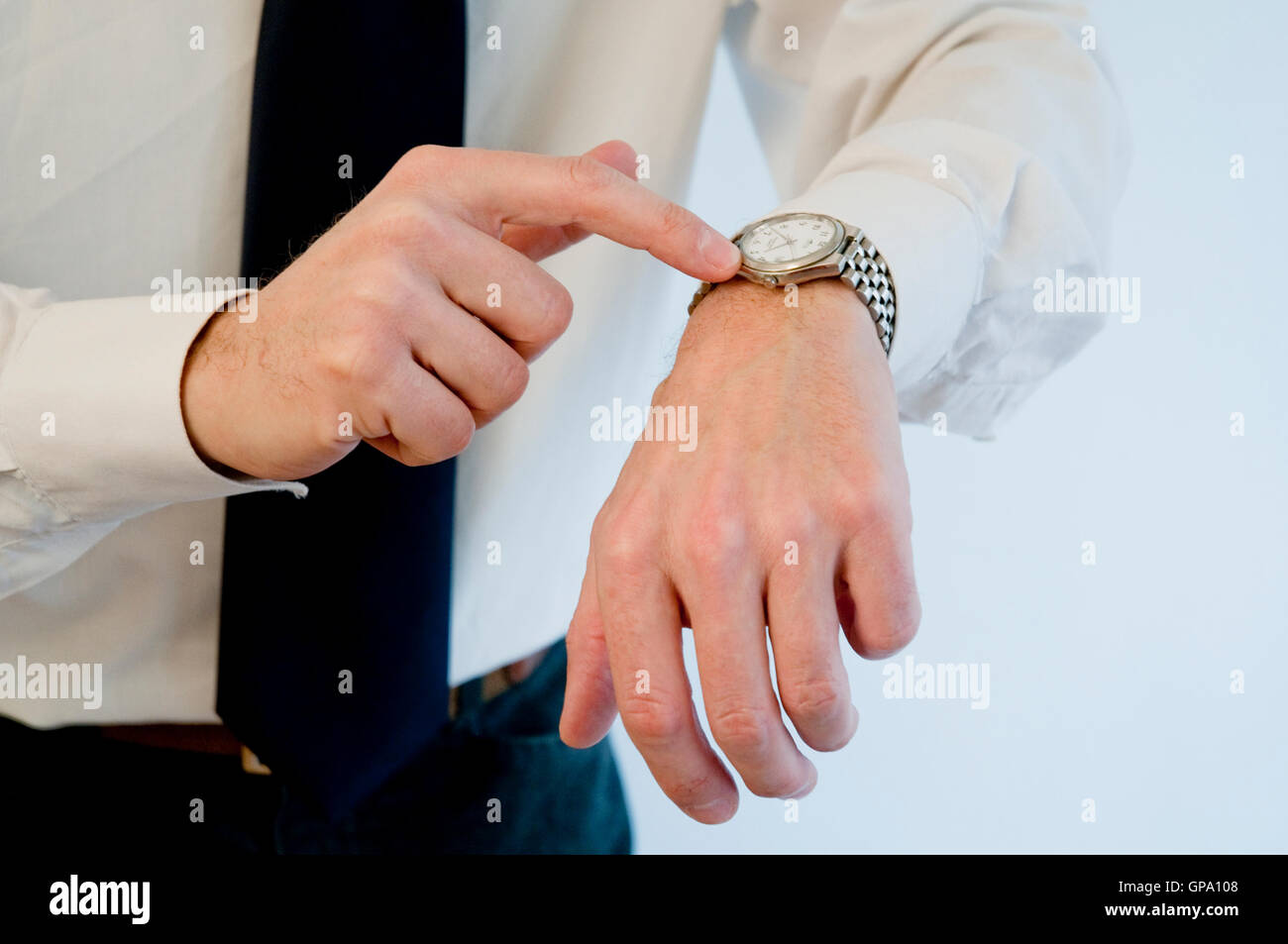 Man's hand pointing his watch. - Stock Image