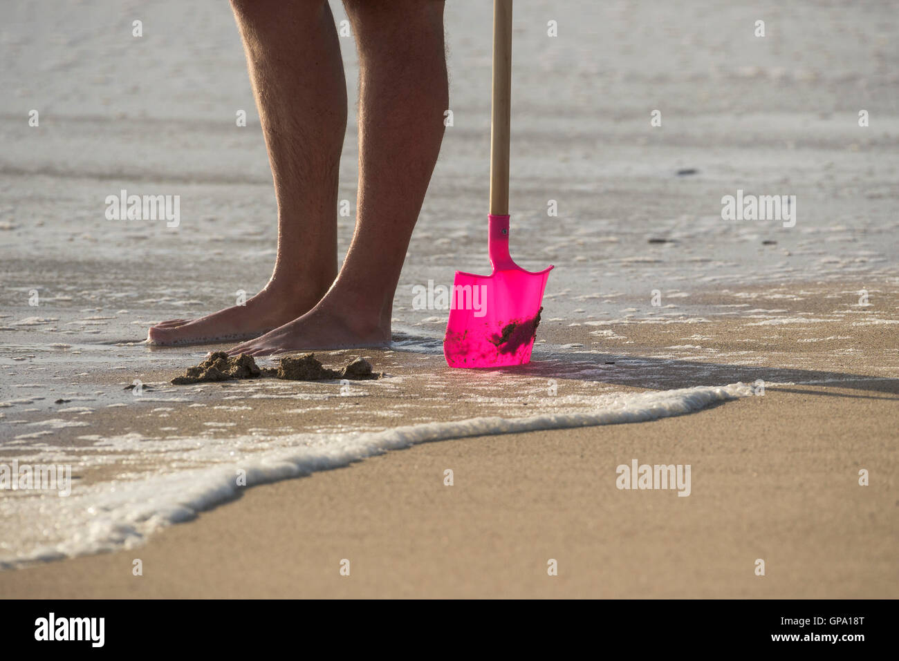 The legs of a holidaymaker standing on Fistral Beach and hiolding a child's plastic spade. Newquay, Cornwall. - Stock Image