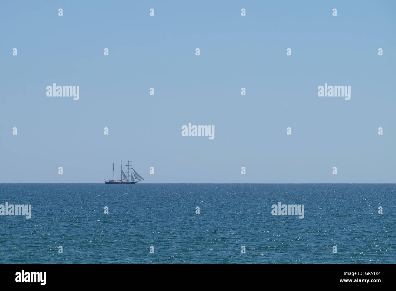 sailing yacht on horizon of blue sea - Stock Image