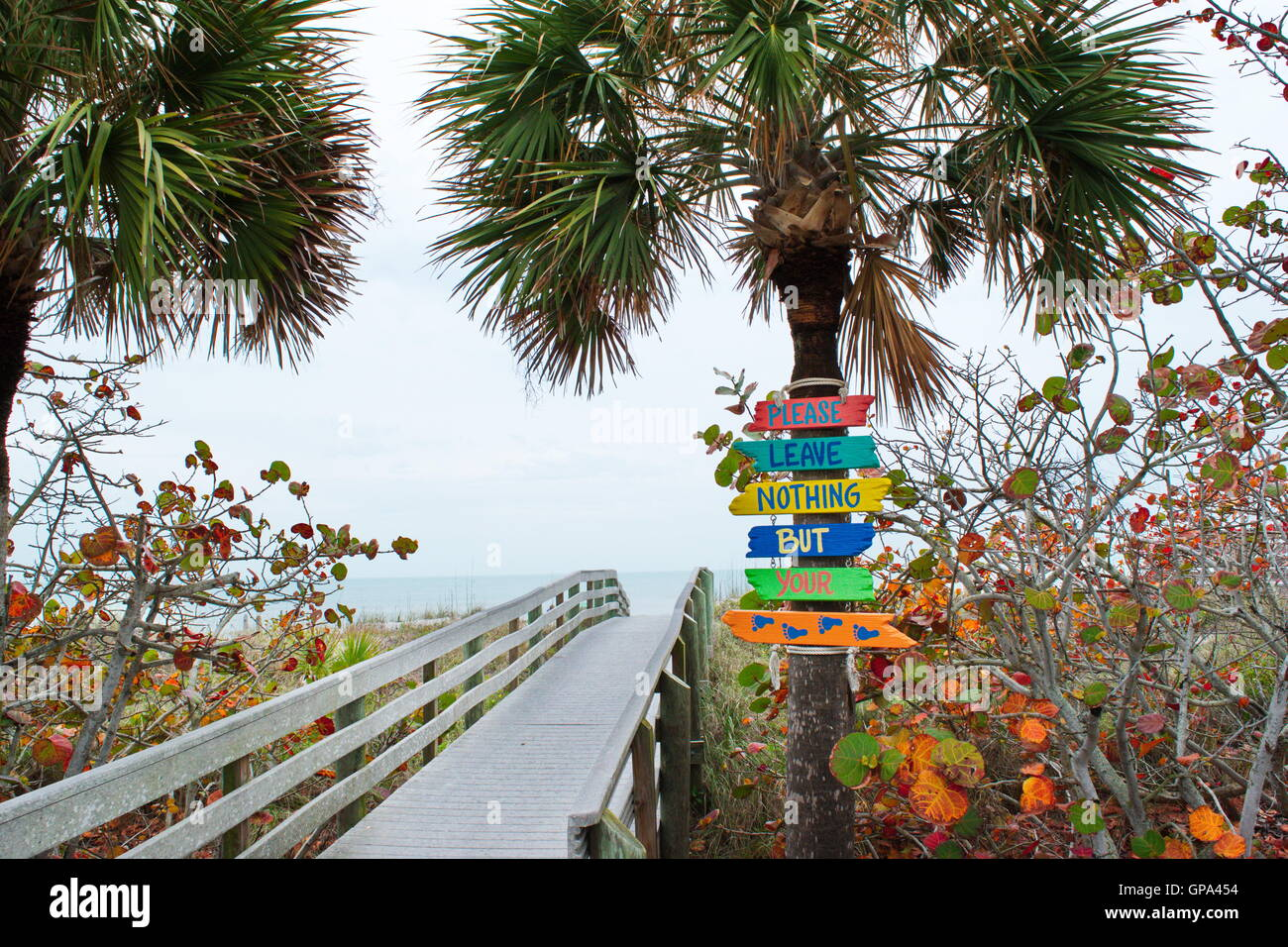 Colorful signs leading to the beach on the Gulf Coast of Florida encourage travelers to not leave any items. - Stock Image