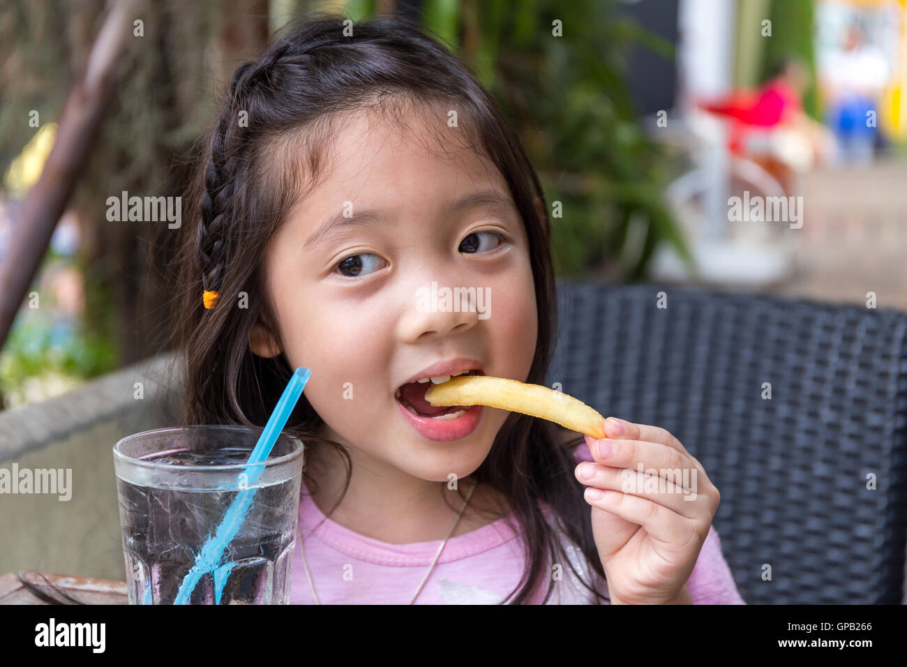 Child eating French fries and water at restaurant. - Stock Image