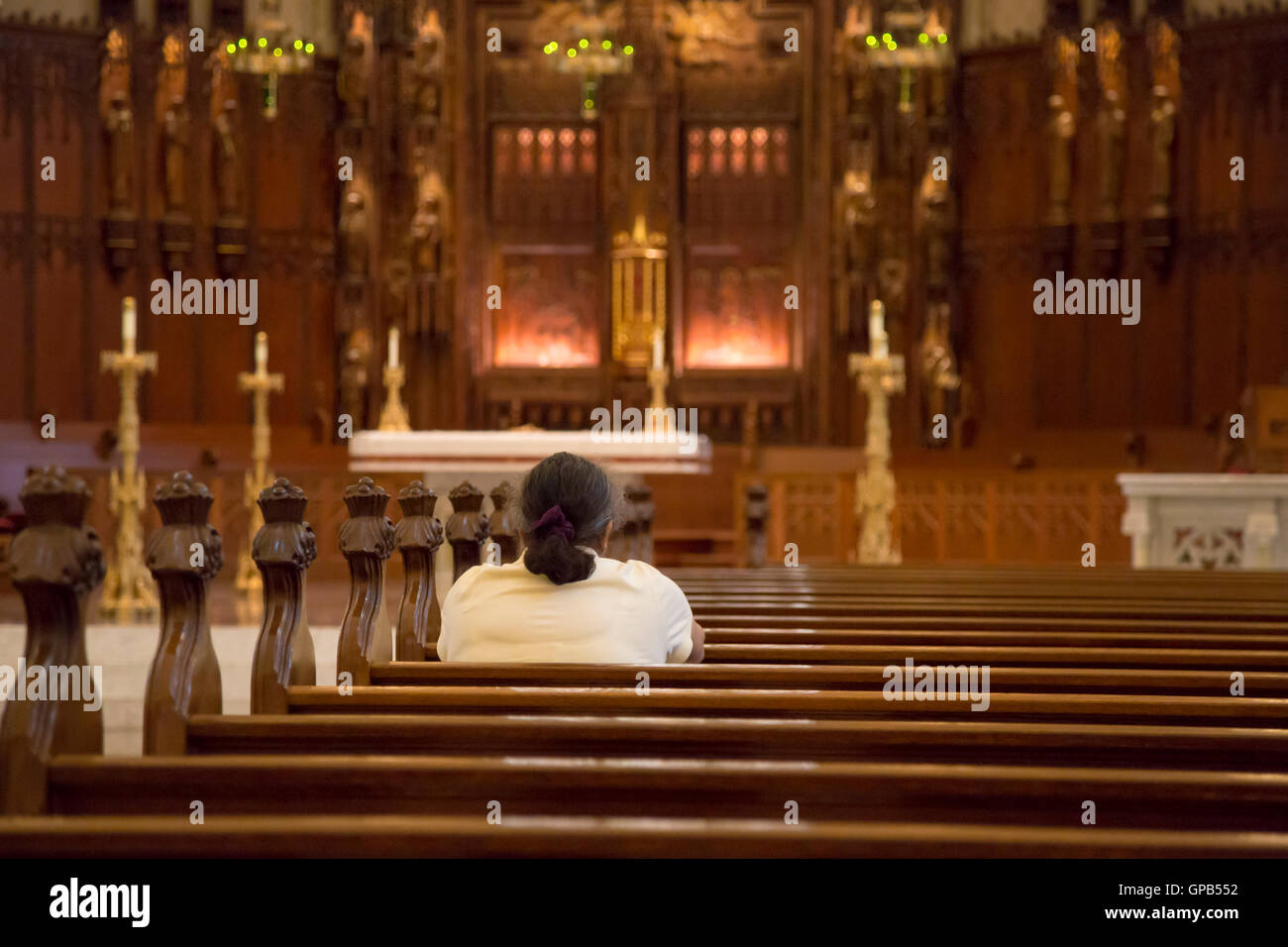 Fort Wayne, Indiana - A woman prays in the Cathedral of the Immaculate Conception. - Stock Image