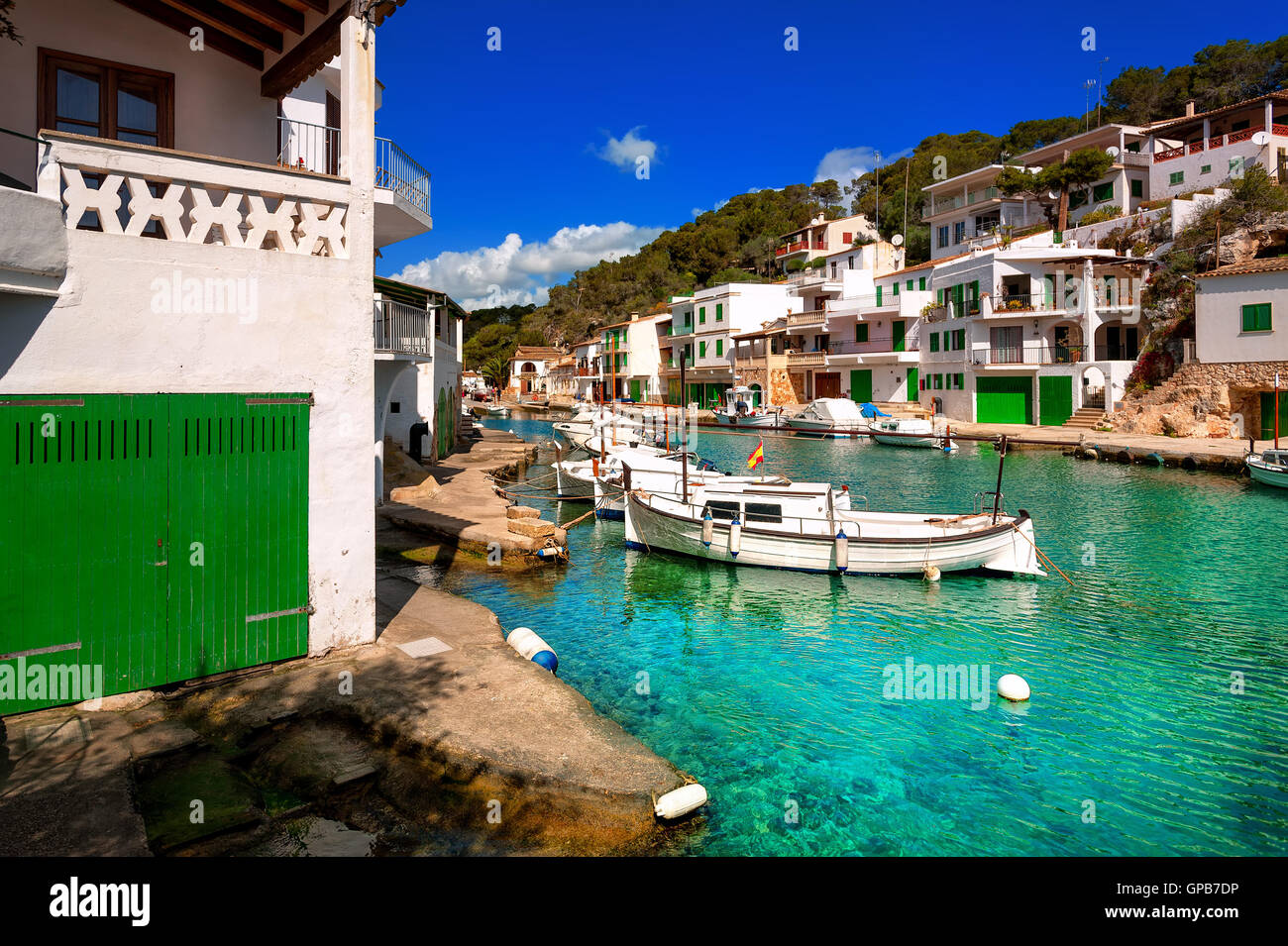 White villas and boats on green water in picturesque fishermen village Cala Figuera, Mediterranean Sea, Mallorca, - Stock Image
