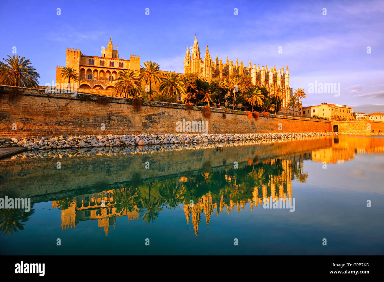 Gothic cathedral La Seu in Palma de Mallorca, Spain, reflecting in the lake water in sunset light - Stock Image