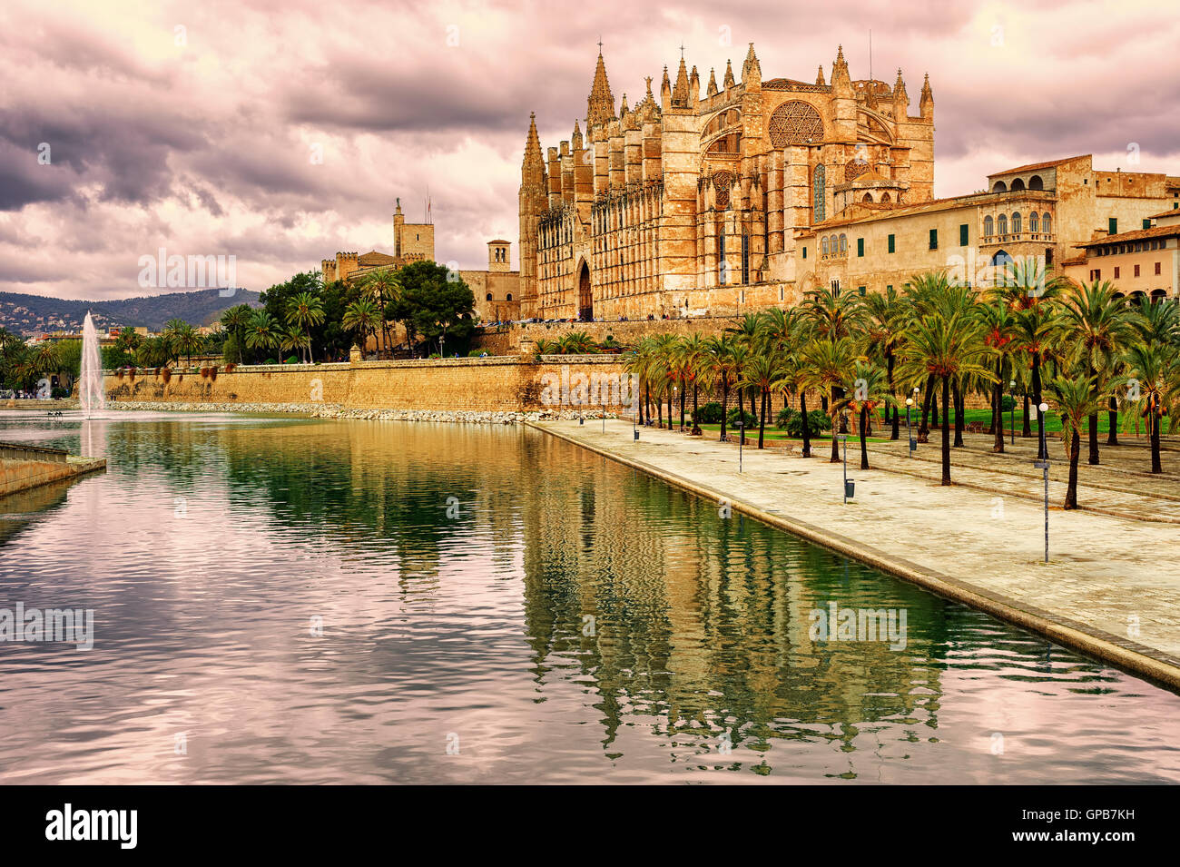 La Seu, the cathedral of Palma de Mallorca, reflecting in the water on sunset, Spain - Stock Image