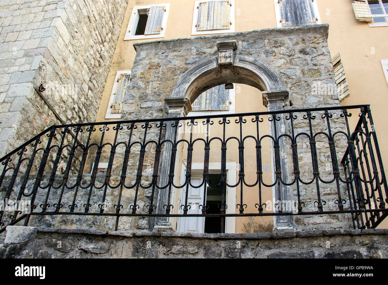 Old Town of Budva, Montenegro - A preserved part of medieval wall with arched doors in front of nineteenth-century - Stock Image
