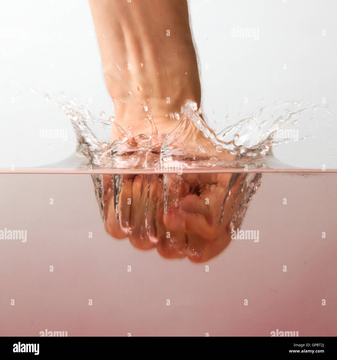 Hand (fist) with splashing red water - Stock Image