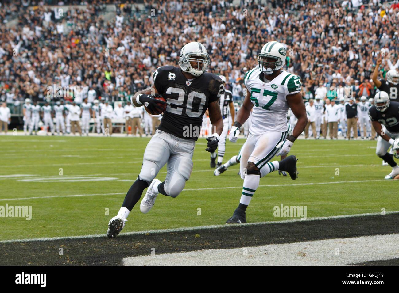 Sep 25, 2011; Oakland, CA, USA;  Oakland Raiders running back Darren McFadden (20) scores a touchdown past New York - Stock Image