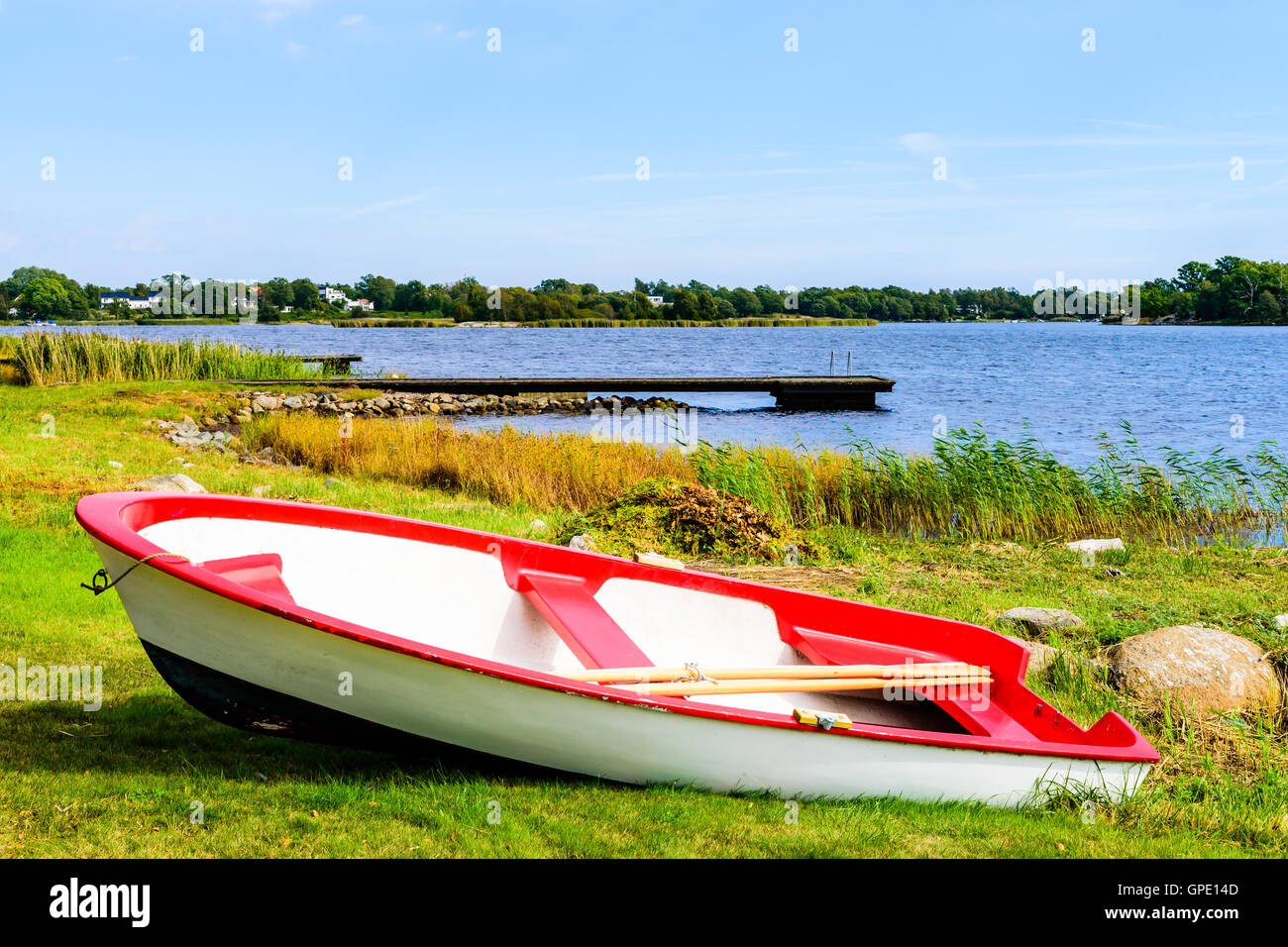 Small red and white rowboat dragged up on land with the coastline in the background.  Skavkulla in Karlskrona archipelago, - Stock Image