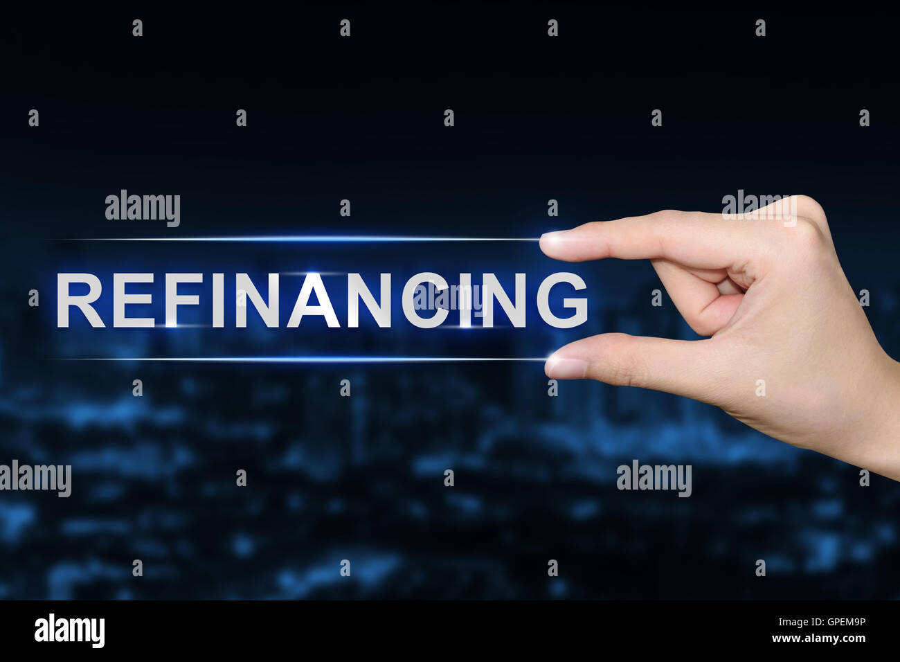 hand pushing refinancing button on blurred blue background - Stock Image
