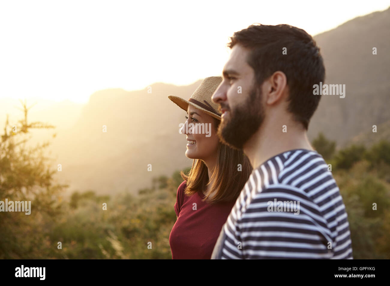 Young couple looking out surrounded by bushes and very bright sun to their left wearing t-shirts and a straw hat - Stock Image