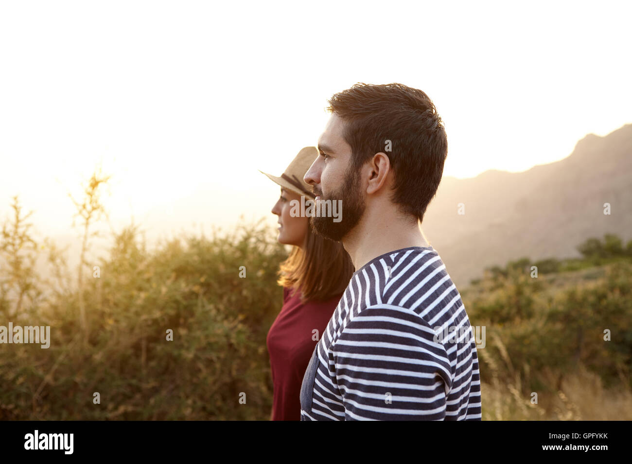 Young couple looking at something surrounded by bushes and very bright sun to their right wearing t-shirts and a - Stock Image
