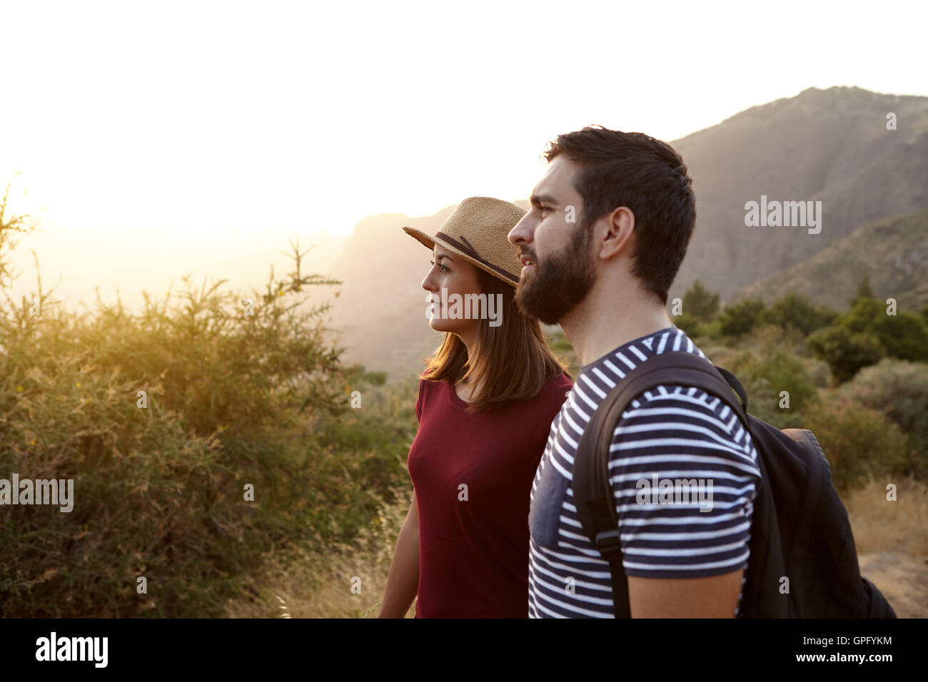 Young couple looking at something far away surrounded by bushes and very bright sun to their right wearing t-shirts - Stock Image