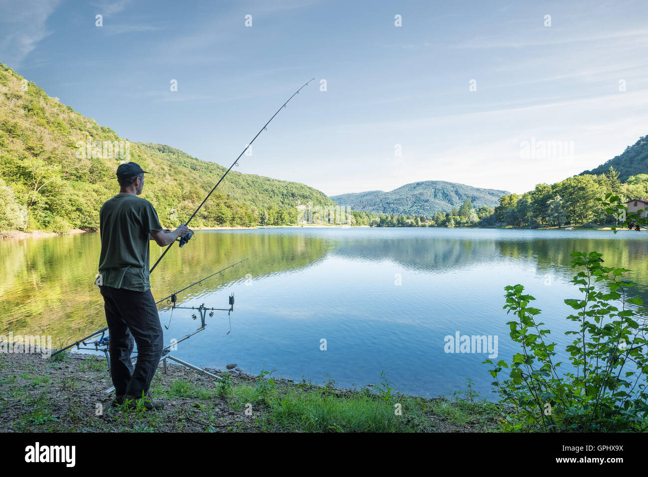 Fishing adventures. Fisherman is fishing on the banks of a lake - Stock Image