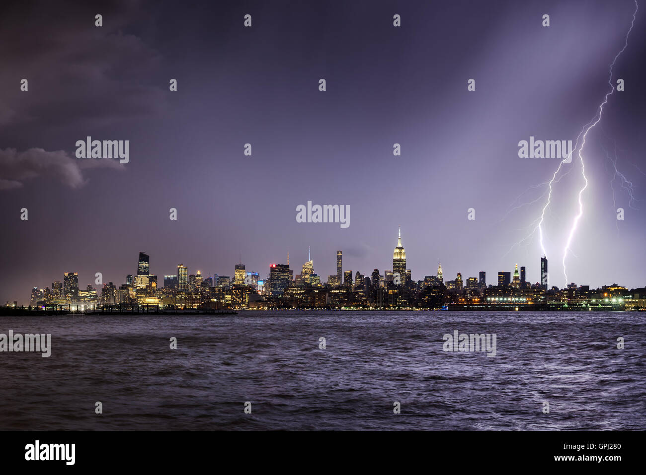 Lightning hitting a New York City skyscraper at twilight. Stormy skies over Midtown West Manhattan from the Hudson - Stock Image