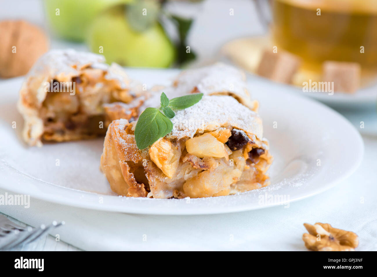 Homemade apple strudel with apples, raisin and walnuts, vegetarian delicious pastry - Stock Image