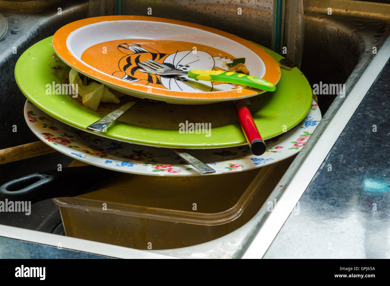 A pile of dirty plates and washing up in the kitchen sink. - Stock Image