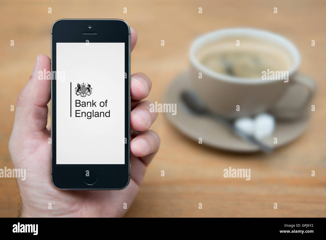 A man looks at his iPhone which displays the Bank of England logo, while sat with a cup of coffee (Editorial use - Stock Image
