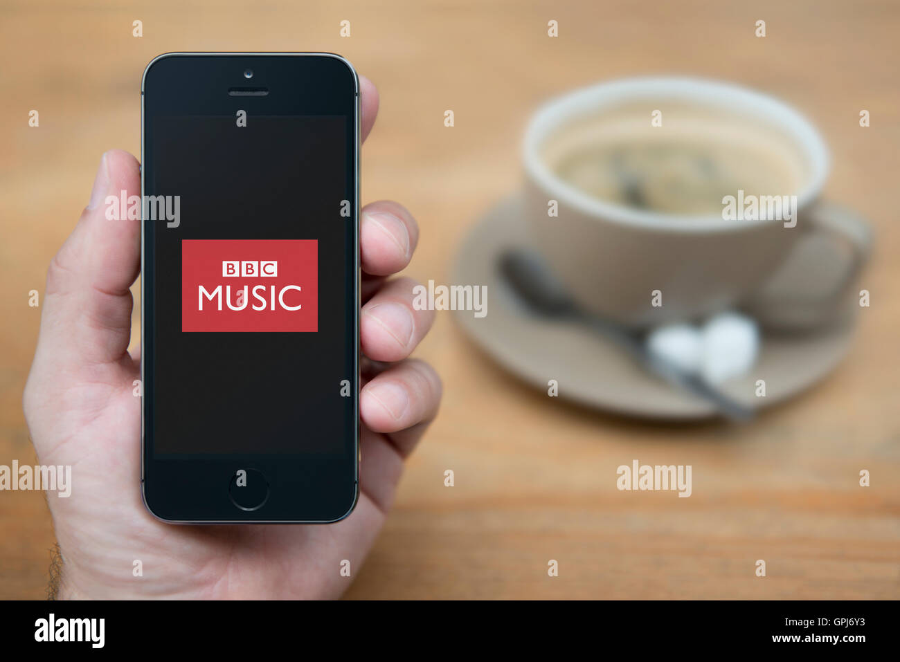 A man looks at his iPhone which displays the BBC Music logo, while sat with a cup of coffee (Editorial use only). - Stock Image