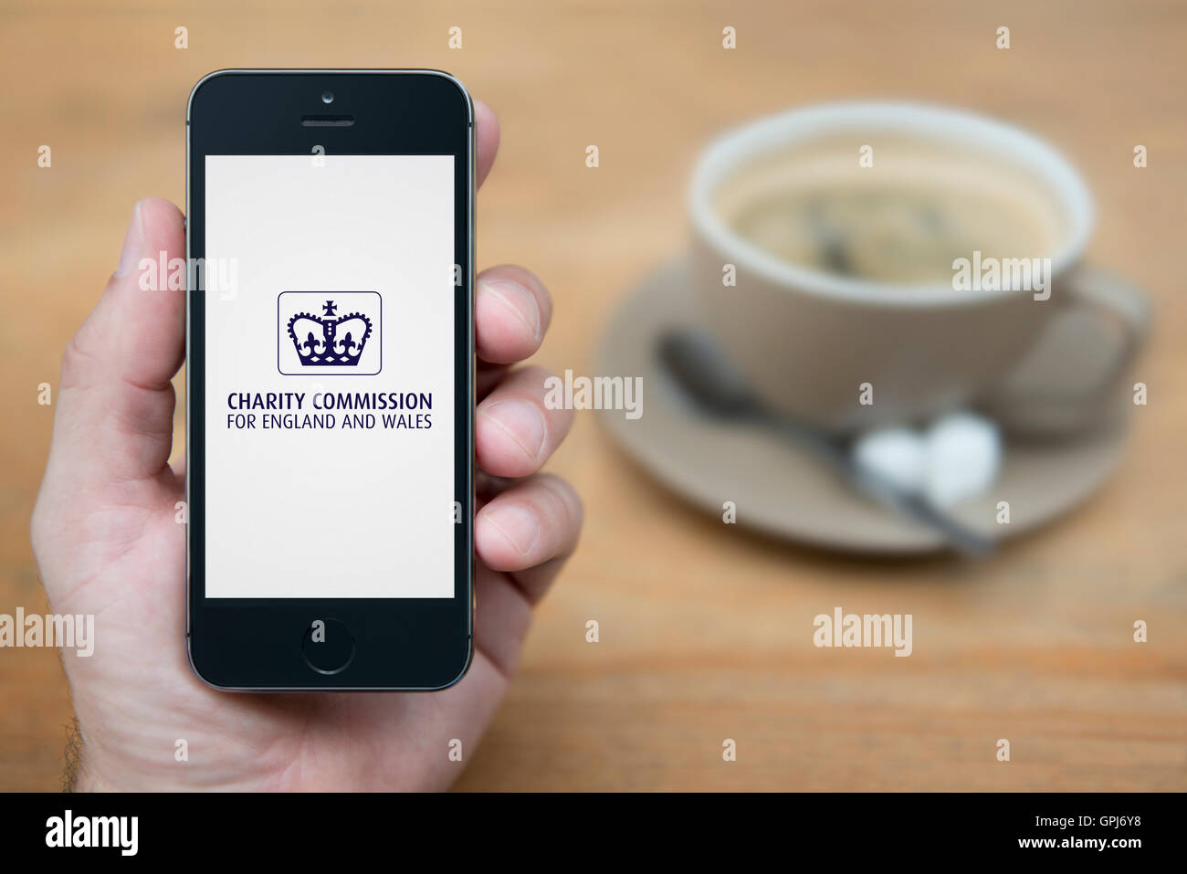 A man looks at his iPhone which displays the UK Government Charity Commission logo, with coffee (Editorial use only). - Stock Image