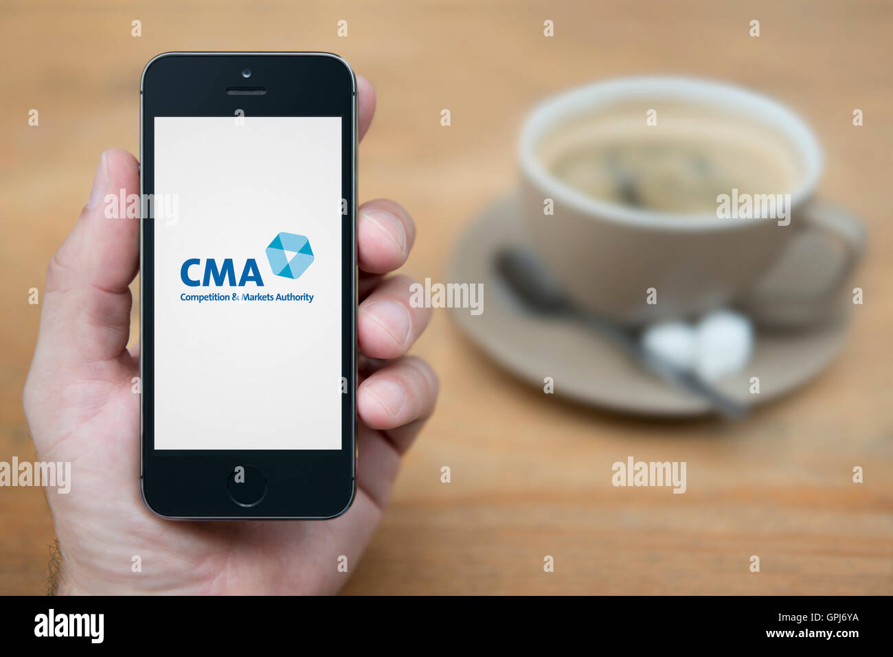 A man looks at his iPhone which displays the UK Government Competition and Markets Authority logo (Editorial use - Stock Image