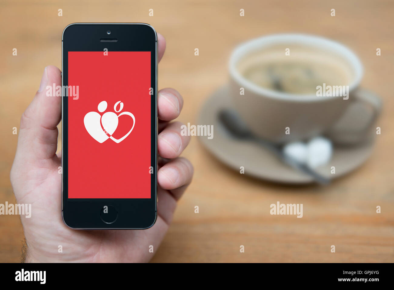 A man looks at his iPhone which displays the Give Blood Donation logo, while sat with a cup of coffee (Editorial - Stock Image