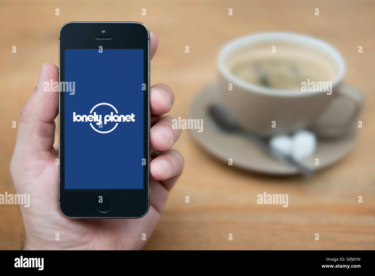 A man looks at his iPhone which displays the Lonely Planet logo, while sat with a cup of coffee (Editorial use only). - Stock Image