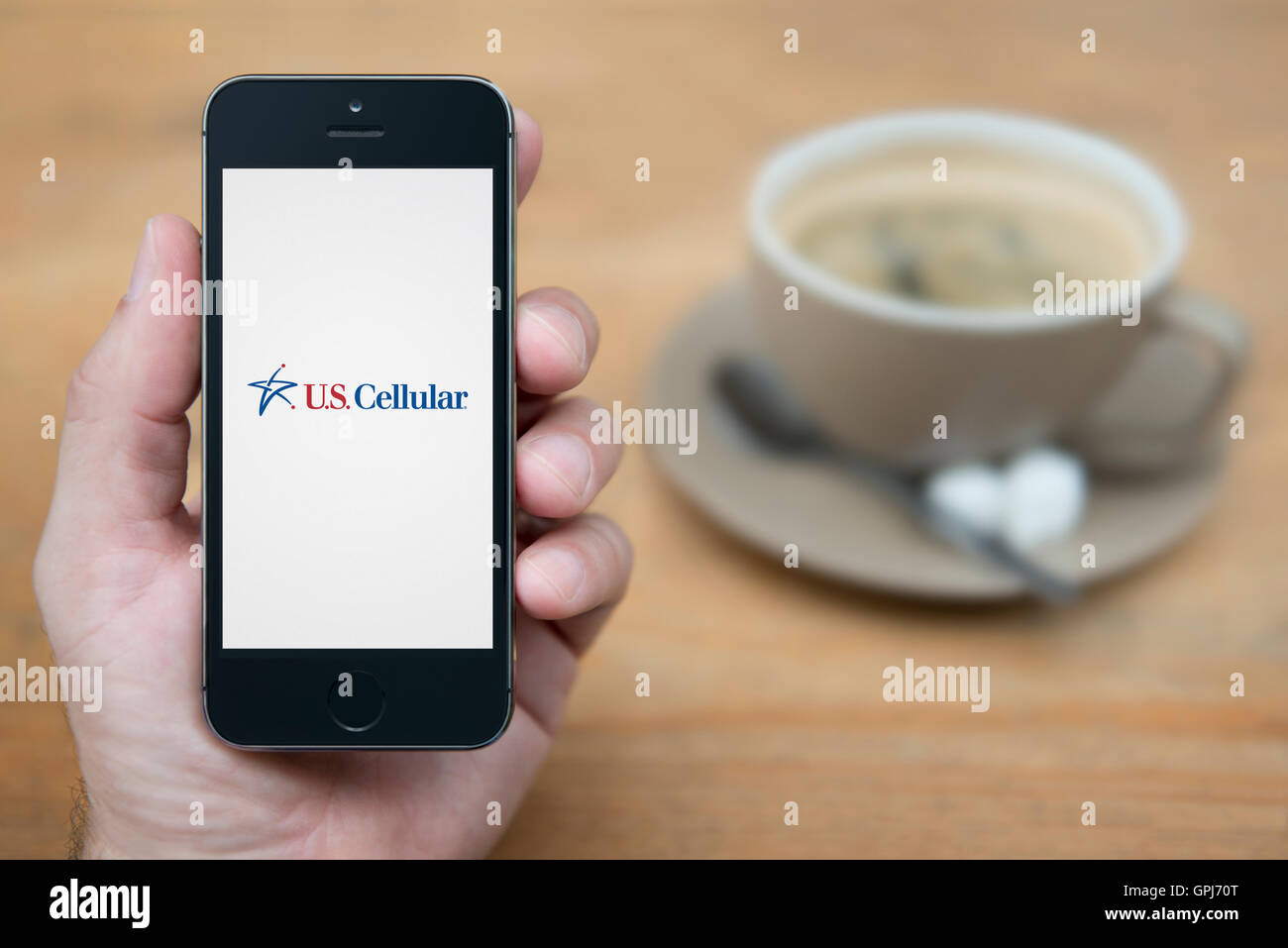 A man looks at his iPhone which displays the U.S.Cellular telecommunications operator logo, with coffee (Editorial - Stock Image