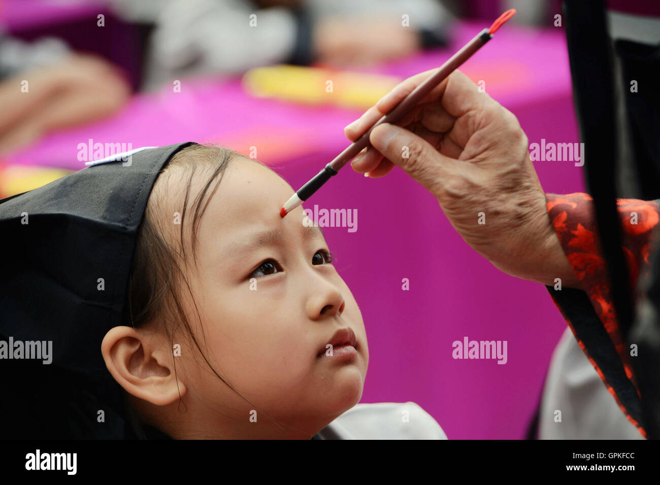 Qingzhou, Qingzhou, China. 5th Sep, 2016. An old scholar of traditional Chinese culture gives a red dot on pupil's - Stock Image