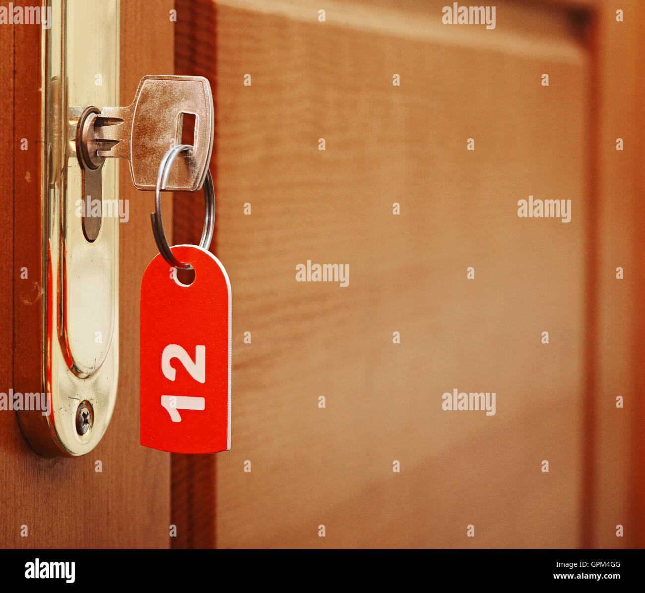 Door handles on wood wing of door and key in keyhole with number - Stock Image
