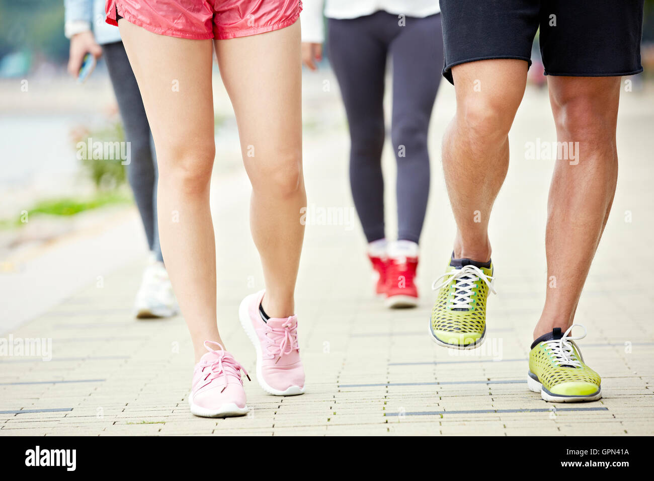 close-up of feet of runners and joggers on a park running trail - Stock Image