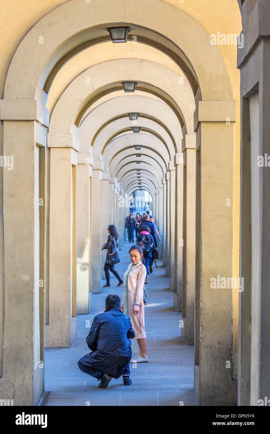 Asian woman being photographed in the Vasari Corridor in Florence, Italy - Stock Image