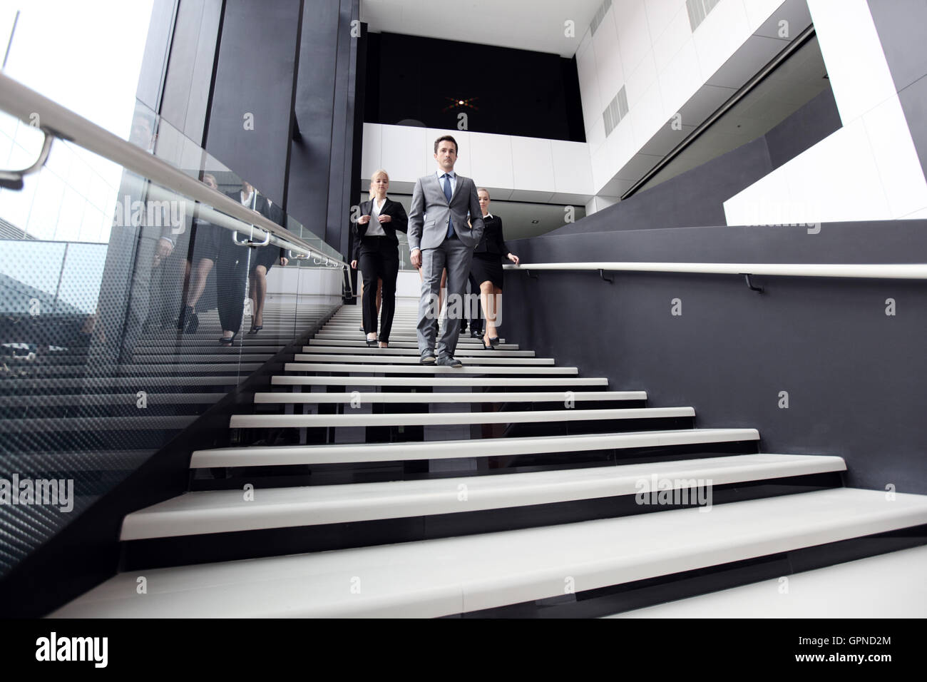 Business people walking down the steps of stairs Stock Photo
