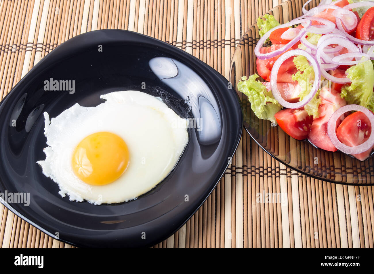 Home-cooked meals on the table - fried egg with yolk on a black plate and a salad of tomato, lettuce and onion on - Stock Image