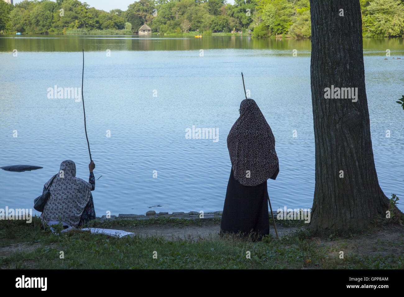 Immigrant Muslim women fish in the lake at Prospect Park, Brooklyn, NY. - Stock Image