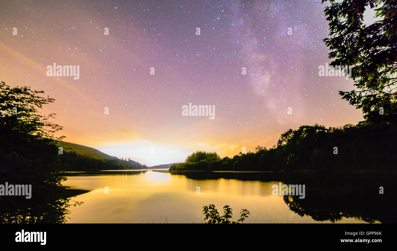 Milky way galactic center over lake landscape in South Wales UK in Plas Dolygaer Stock Photo