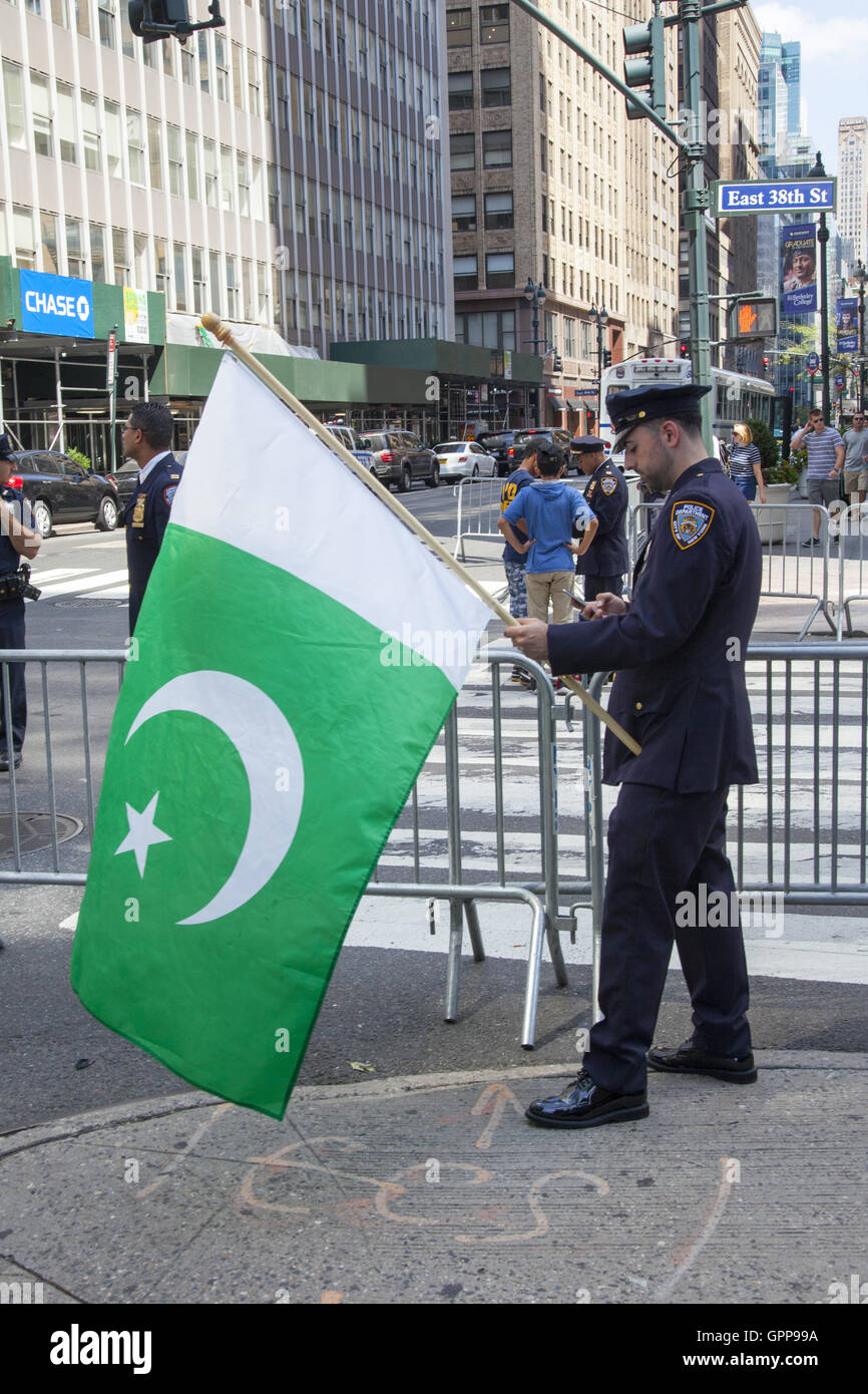 Pakinstani NYPD police officer holds a Pakistani flag ready