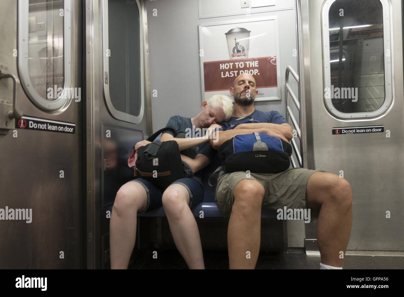 Tired couple take a cat nap on the F Train in Brooklyn, New York. - Stock Image