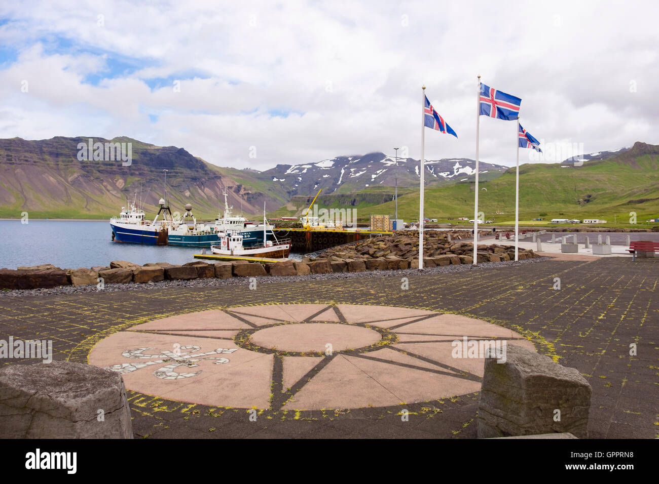 Icelandic flags flying on the quay with fishing boats moored in the harbour. Grundarfjordur, Snaefellsnes Peninsula, - Stock Image