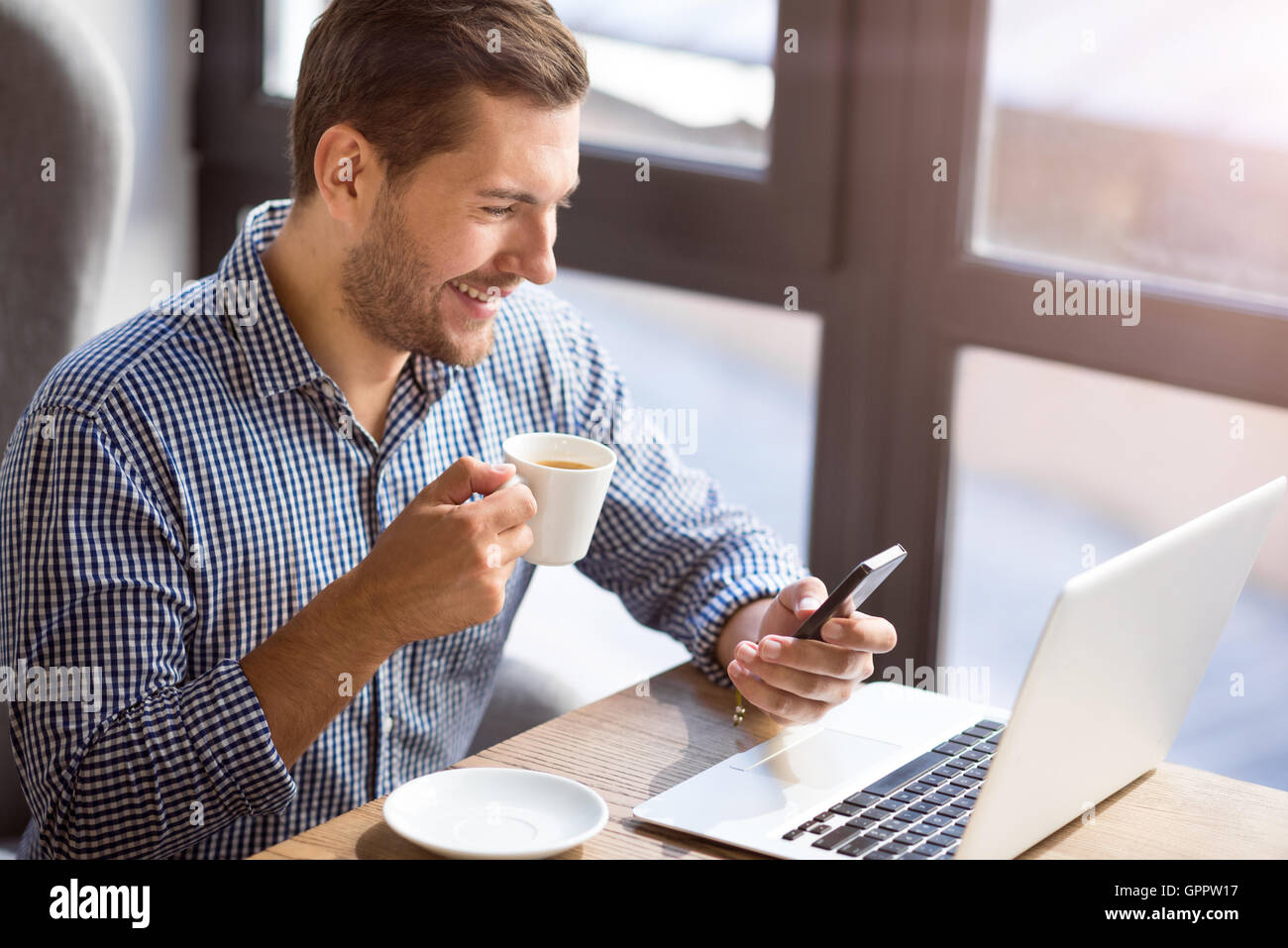 Cheerful man sitting at the table - Stock Image