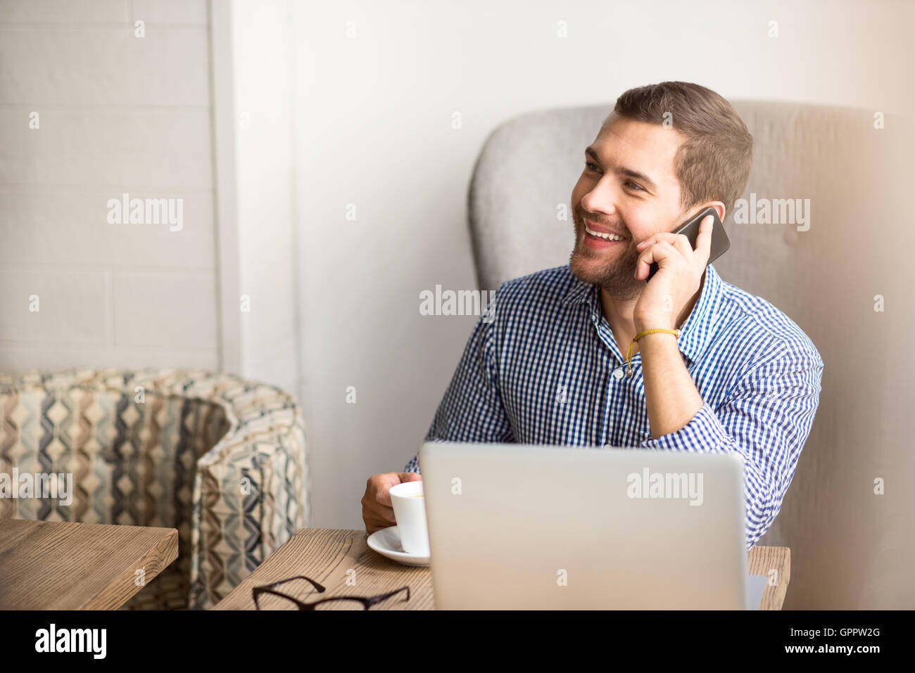 Cheerful man resting in the cafe - Stock Image