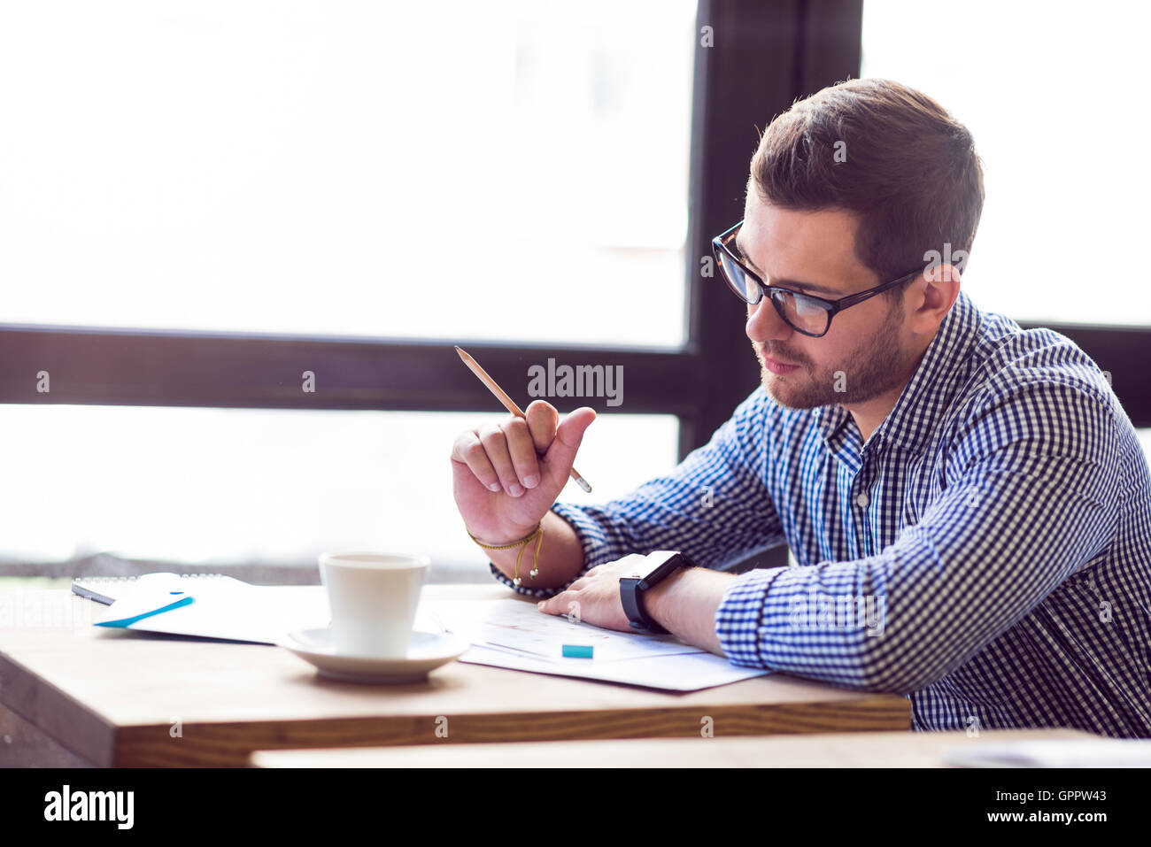 Thoughtful serious man working at the table - Stock Image