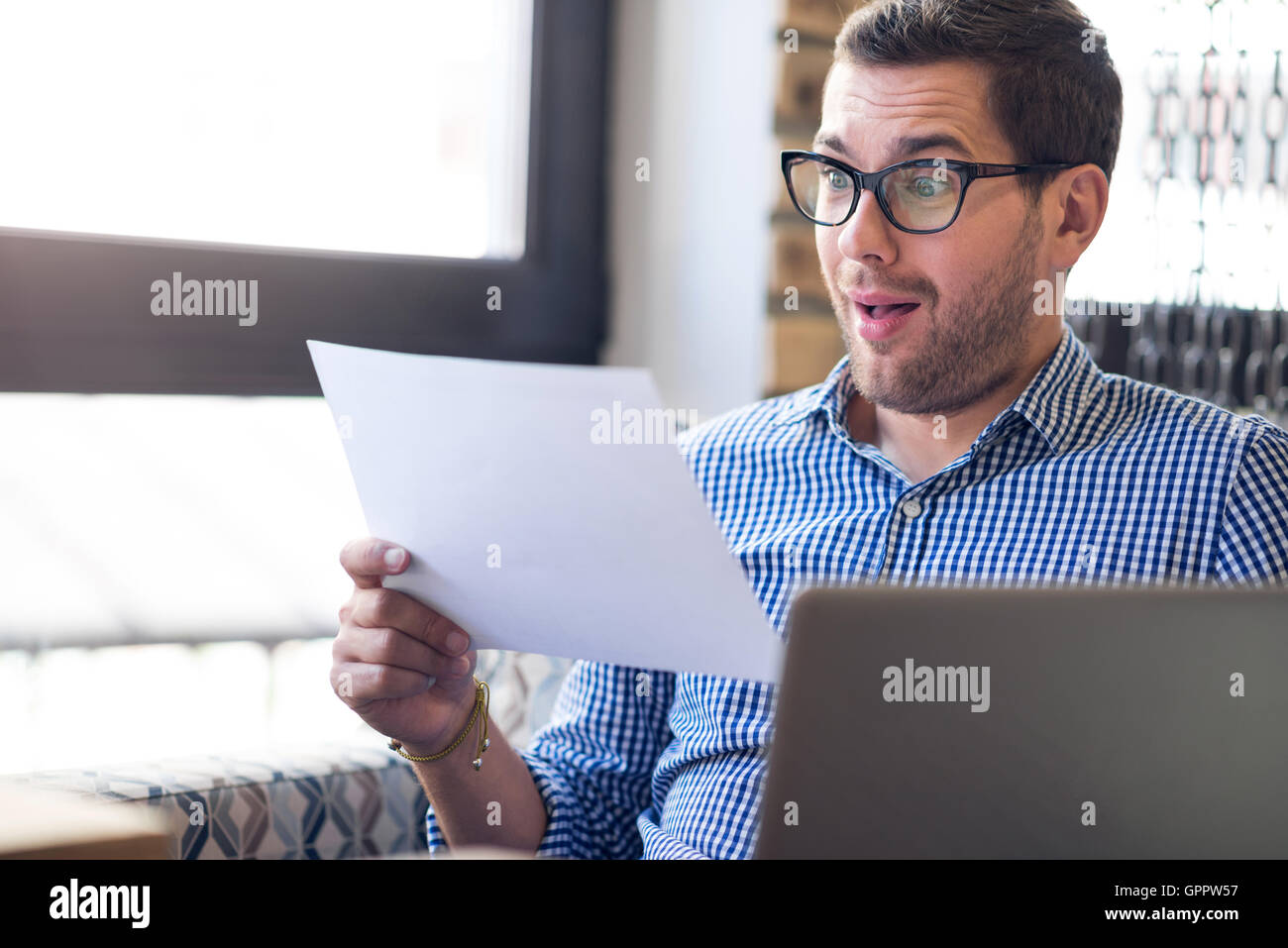 Positive emotional man holding papers - Stock Image